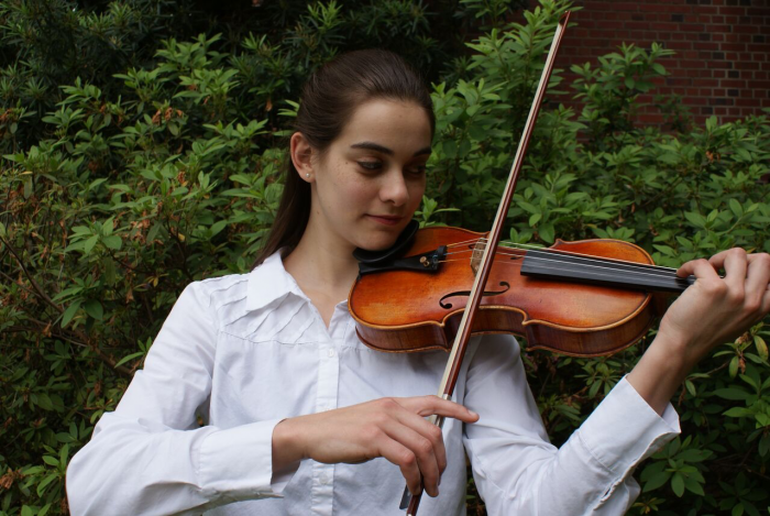 Robin Tozzie, Concerto Competition Winner, College Division Violin, posing with her violin